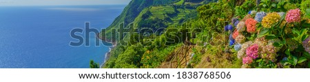 Viewpoint Ponta do Sossego, Sao Miguel Island, Azores, Portugal. View of flowers on a mountain and the ocean in Miradouro da Ponta do Sossego Nordeste, Sao Miguel, Azores, Portugal., Panorama Royalty-Free Stock Photo #1838768506