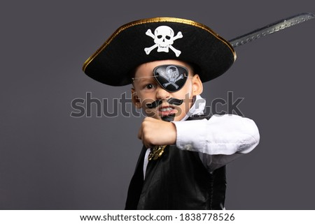 The classic pirate captain character, brandishing a saber. A boy on Halloween dressed in a pirate costume. Halloween holiday concept on gray background