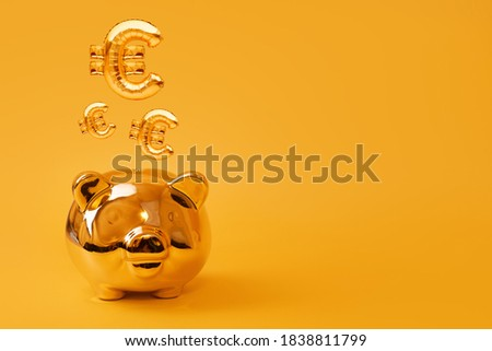 Golden piggy bank on yellow background with Gold Euro Sign Balloons. Golden currency symbol made of inflatable foil balloon. Investment and banking concept.Money saving, moneybox, finance, investments
