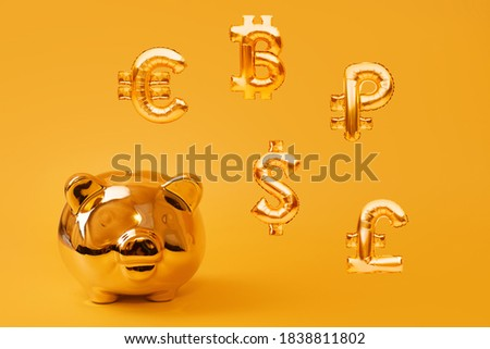 Golden piggy bank on yellow background with golden currency symbols made of inflatable foil balloons. Investment and banking concept. Money saving, moneybox, finance, investments