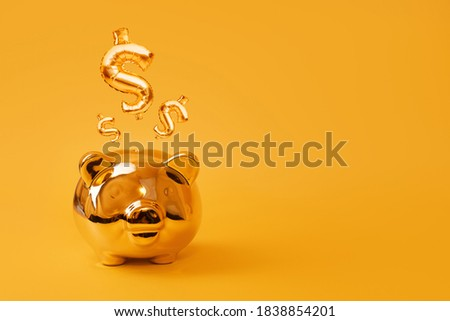 Golden piggy bank on yellow background with Gold USD Sign Balloons. Golden currency symbol made of inflatable foil balloon. Investment and banking concept.Money saving, moneybox, finance, investments