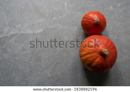 Bright orange halloween pumpkins Jack O' Lanterns on grey marble stone background. Top view pumpkin fall picture with copy space. Flat lay, scandinavian style.