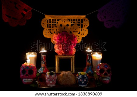 Day of the Dead offering from central Mexico with papel picado, veladoras, photography, flowers and bread of the dead Royalty-Free Stock Photo #1838890609