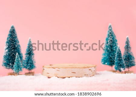 Mock up with wooden podium from a circle of wood on trendy pastel pink background with christmas decoration tree. Place for christmas product presentation