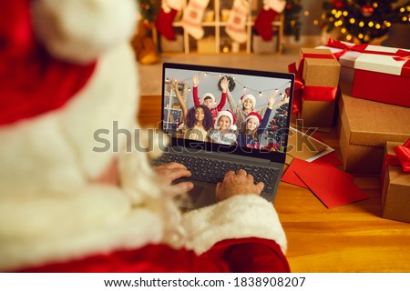 Over shoulder view of Santa Claus or Father Christmas having video call with happy diverse children on laptop computer in his workshop. Self-isolation and virtual online celebration at home concept #1838908207