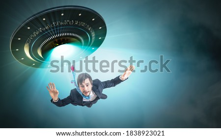 Alien abduction concept. Young man is abducted by UFO. Royalty-Free Stock Photo #1838923021