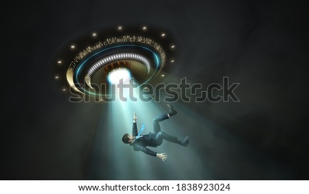 Alien abduction concept. Young man is abducted by UFO. Royalty-Free Stock Photo #1838923024