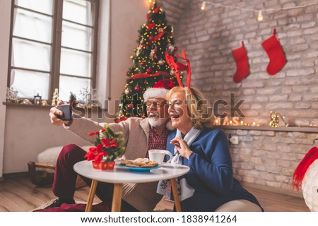 Senior couple having fun while having virtual party with friends and family on Christmas day; elderly couple having video call with children while celebrating Christmas #1838941264