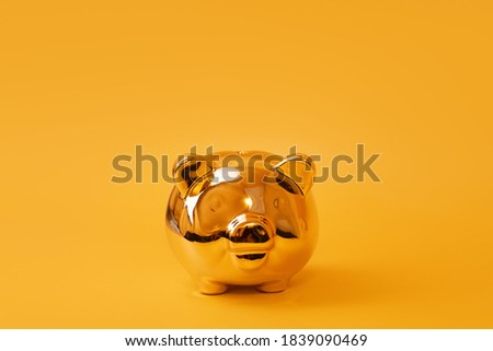 Golden piggy bank on yellow background. Golden money box. Money pig, money saving, moneybox, finance and investments concept. Free space for text