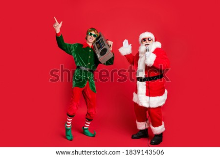 Photo of two carefree people elf hold vintage radio santa sing microphone wear sunglass x-mas costume coat cap isolated red color background