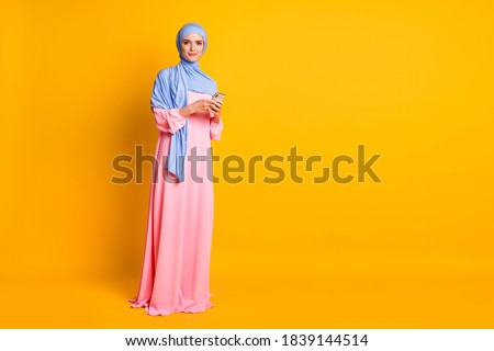 Full length body size view of nice pretty elegant muslimah wearing hijab dress using device blog isolated on bright yellow color background