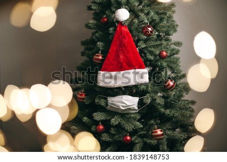 Christmas tree decorated with red balls, medical white masks and a Santa hat. Coronavirus pandemic, quarantine, 2020, 2021. New Year celebration, holiday, self-isolation, stay at home. Royalty-Free Stock Photo #1839148753