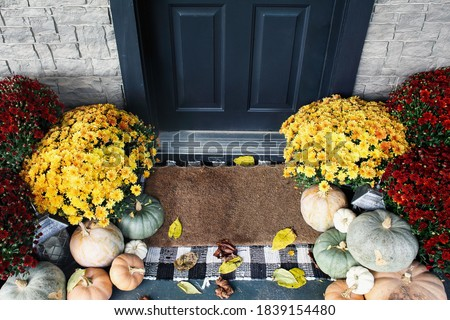 Welcome door mat of front porch that has been decorated for autumn with heirloom white, orange and grey pumpkins and mums.
