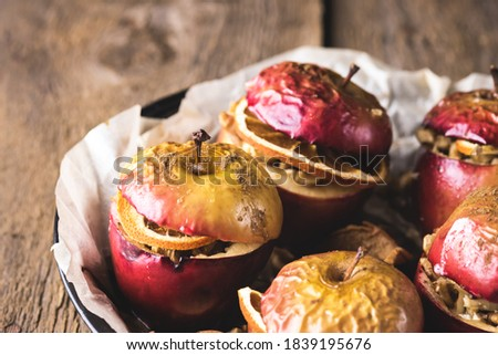 Homemade Oven Baked Apples Stuffed with Nuts Orange Chips and Honey in Baking Pan Old Wooden Background Healthy Autumn or Christmas Dessert Horizontal #1839195676