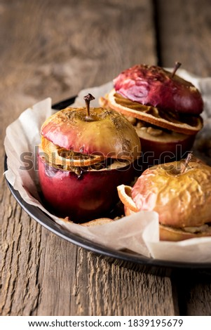 Homemade Oven Baked Apples Stuffed with Nuts Orange Chips and Honey in Baking Pan Old Wooden Background Healthy Autumn or Christmas Dessert Vertical #1839195679