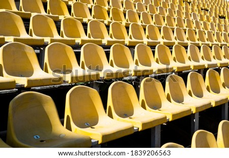 chairs for audience. cultural environment concept. color and symmetry. empty seats. modern stadium. yellow tribunes. seats of tribune on sport stadium. empty outdoor arena. concept of fans. Royalty-Free Stock Photo #1839206563