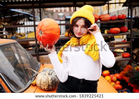 Fall photoshoot ideas. Planning for Thanksgiving. Fashionable beautiful young teen girl at the autumn pumpkin patch background.