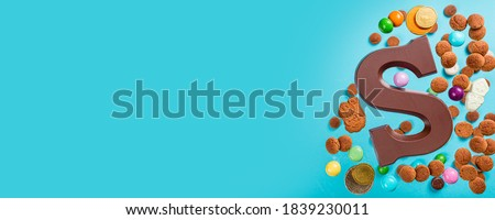 Dutch holiday Sinterklaas background with chocolate letter, kruidnoten cookies and traditional hollands sweets. Concept for children party Saint Nicholas day five december with copy space. Banner Royalty-Free Stock Photo #1839230011