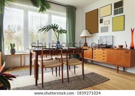 Modern scandinavian home interior of living room with design retro furniture, tropical palm, gallery wall, decoration and elegant personal accessoreis in stylish home decor. Royalty-Free Stock Photo #1839271024
