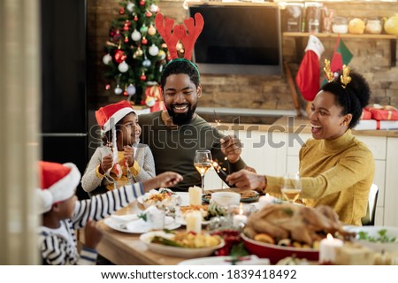 Joyful African American family using sparklers while having lunch and celebrating Christmas at dining table.  #1839418492