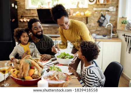 Happy African American woman having Thanksgiving lunch with her family and serving salad at dining table.  #1839418558