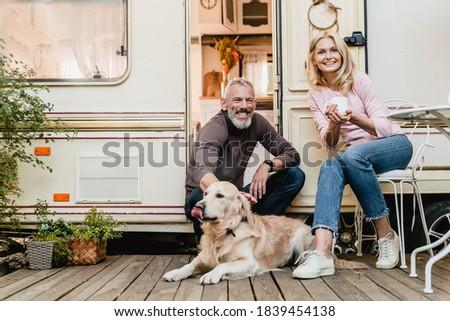 Portrait of senior joyful smiling european couple with their labrador resting in the doorway of their caravan home