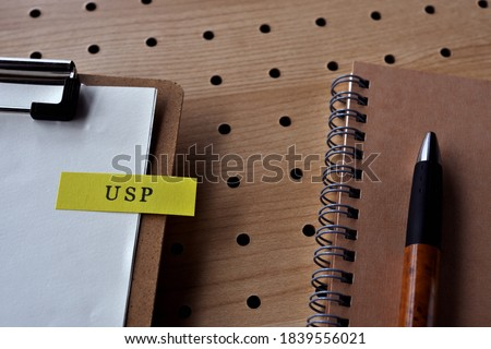 There is a notebook, a pen, and a clipborad with a sticky note stuck to it that says USP written on it. It was an abbreviation for Unique Selling Proposition.