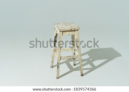 Tall retro stool or tabouret with peeling white paint on white background. Empty place. #1839574366