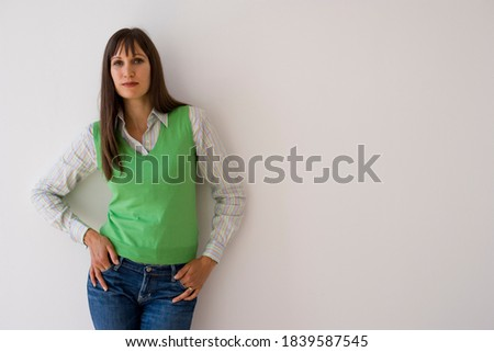 Horizontal three quarter front view of a young woman with hands in pockets wearing a green sweater vest smiling at the camera with copy space.