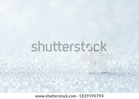 White snowflake on silver blurred background. Selective focus. Macro, minimalism concept. Christmas or winter greeting card, poster. Image for notebook cover.  Xmas and Happy New Year holiday.
