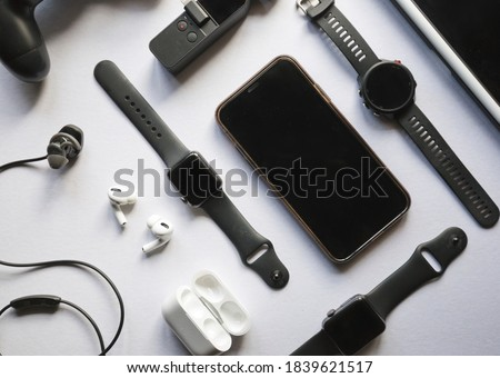 Flat lay shot of gadgets and mobile devices in white background.  Royalty-Free Stock Photo #1839621517