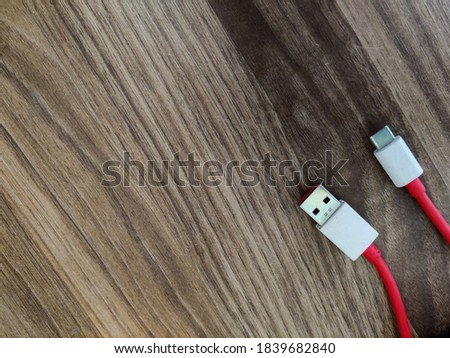 Data transfer cable or charging cable on a wood table.