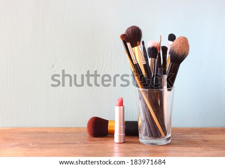 make up brushes over wooden table  #183971684