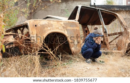 A little girl is crying near the burnt car. War in Donetsk. War Nagorno-Karabakh. Burned-out car. Royalty-Free Stock Photo #1839755677