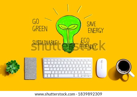 Green light bulb with a computer keyboard and a mouse
