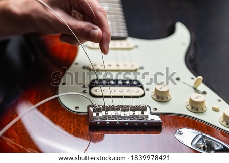 Replacing strings on an electric guitar Royalty-Free Stock Photo #1839978421