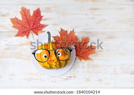 funny pumpkin in eyeglasses on plate with maple leaves, on white wooden table. fall harvest season, thanksgiving holiday, Halloween concept. flat lay