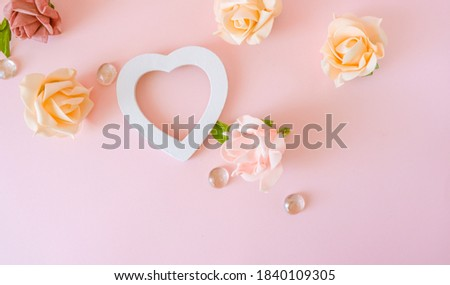 Roses background with white heart flame. Various pink roses flowers buds and petals scattered on pastel pink background, overhead view, copy space flat lay .Flowers composition. Frame made of rose fl