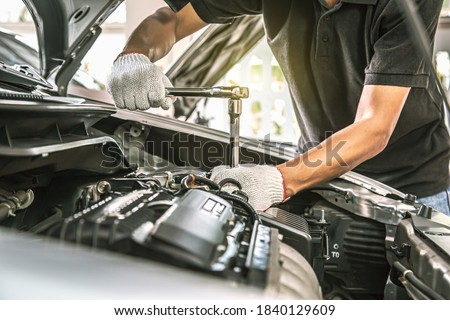 Close-up hands of auto mechanic are using the wrench to repair a car engine in auto car garage. Concepts of car care fixed repair and services. Royalty-Free Stock Photo #1840129609