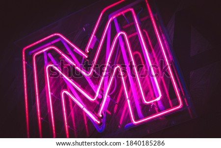 Restaurant sign decorate neon color red and purple are denoted to the letter M.
