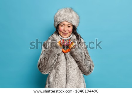 Cheerful eskimo woman shapes heart gesture expresses love dressed in warm winter clothing isolated over blue background. Affectionate reindeer herder in fur outerwear. Nothern people and cold season Royalty-Free Stock Photo #1840194490