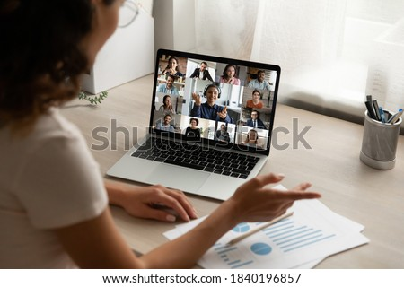 Back view of female employee talk speak on team video call with diverse colleagues coworkers. Woman worker have webcam digital virtual conference at home office, engaged in online group meeting. Royalty-Free Stock Photo #1840196857