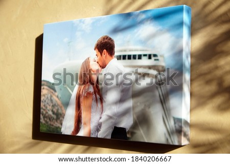 Canvas print with gallery wrap technique on biege wall with natural light shadow of leaves. Wedding photo printed on canvas, wall decor. Stretched photography, portrait of a kissing couple