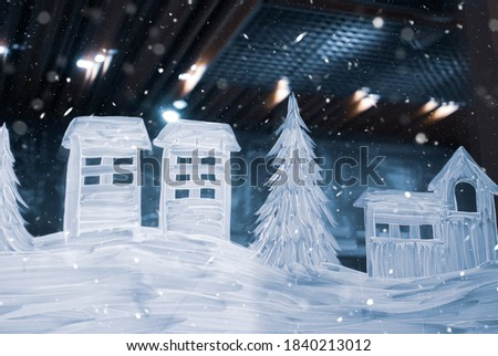 Winter drawing on the window. Snow-covered houses and white Christmas trees