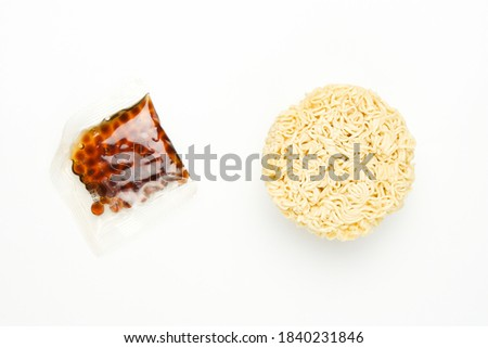 Flatlay picture of round instant noodle with tapioca ball on white background. New and trending food instant noodle serve in spicy pearl milk or boba tea.