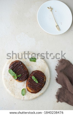 A picture focus on two chocolate cheese cake topped with chocolate glaze and mint leaves for garnish in marble board and grainy background