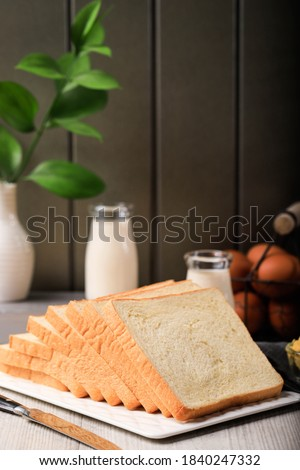 Sliced Toast Loaf White Bread (Shokupan or Roti Tawar) for Breakfast on Wooden Background, Served with Egg and Milk. Bakery Concept Picture