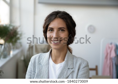Close up headshot portrait of smiling successful Caucasian woman fashion designer or tailor pose in home office. Profile picture of happy confident stylist or architect look at camera work in atelier.