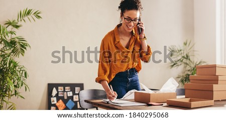 Drop shipping business owner talking on mobile phone and taking order. Female entrepreneur working at home office confirming the order on phone. Royalty-Free Stock Photo #1840295068