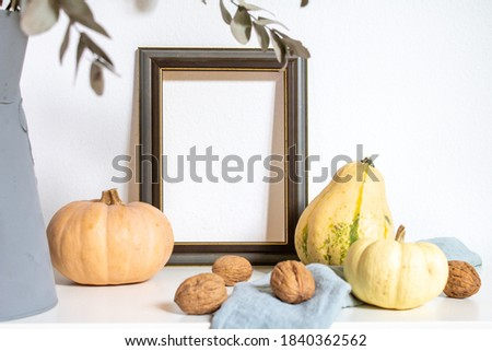 Fall image with pumpkins, nuts and picture frame